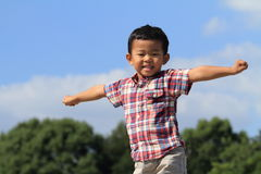 Smiling Japanese boy under the blue sky Royalty Free Stock Image