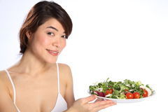 Smiling Japanese girl holds out plate green salad Stock Image