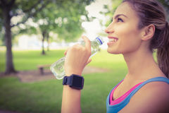 Smiling jogger woman drinking water in park Stock Image