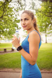Smiling jogger woman holding water bottle in park Stock Photos