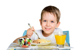Smiling joyful boy sitting at the dinner table and looking at th Royalty Free Stock Photography