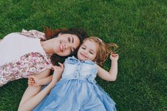 Smiling joyful woman in light dress and little cute child baby girl lie on green grass in park rest, have fun. Mother. Smiling joyful women in light dress and royalty free stock images