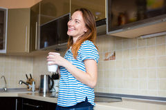 Smiling joyful young female  standing in kitchen and drinking tea Royalty Free Stock Image
