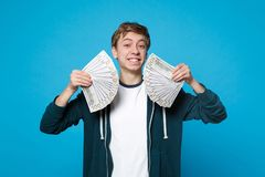 Smiling joyful young man in casual clothes holding fan of money in dollar banknotes, cash money isolated on blue stock images