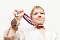 Smiling karate champion child boy gesturing for victory triumph. Martial art sport success and win concept - smiling karate champion child boy hand holding first Royalty Free Stock Photos
