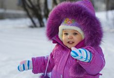 Smiling kid. The small girl in winter in a pink overalls Royalty Free Stock Images