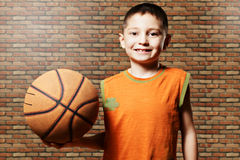 Smiling kid with basketball. Standing against wall Stock Photography