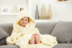 Smiling kid in bathrobe at home sofa bare feet. Happy smiling caucasian kid sitting in oversized bathrobe at home sofa, bare feet. Indoor, relaxed. Hood over Royalty Free Stock Image
