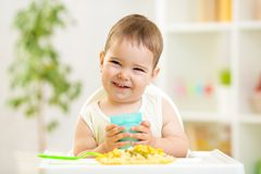 Smiling kid boy eating indoors Stock Images