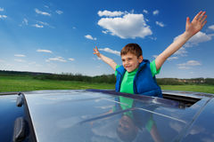 Smiling kid boy enjoying freedom on sunroof of car. Portrait of happy smiling five years old boy enjoying freedom on the sunroof of a car Royalty Free Stock Photo