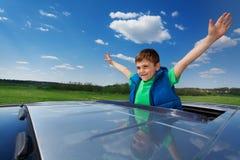 Smiling kid boy enjoying freedom on sunroof of car Royalty Free Stock Photo