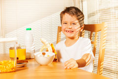Smiling kid boy holding banana in the kitchen Royalty Free Stock Photography
