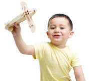 Smiling kid boy playing wooden airplane toy Royalty Free Stock Images