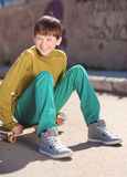 Smiling kid boy sitting on skateboard outdoors Royalty Free Stock Image