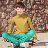Smiling kid boy sitting on skateboard outdoors Stock Photography