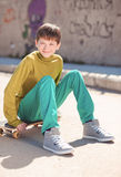 Smiling kid boy sitting on skateboard outdoors Royalty Free Stock Photography