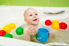 Smiling kid boy taking bath and playing with toys Royalty Free Stock Images