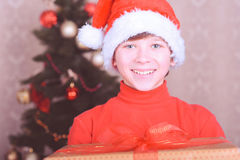 Smiling kid boy wearing santa hat over christmas lights Royalty Free Stock Photos