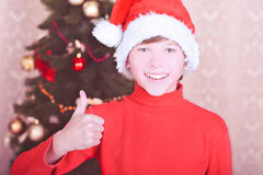Smiling kid boy wearing santa hat over christmas lights Stock Photography