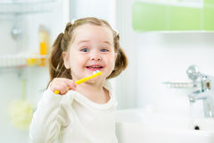 Smiling kid brushing teeth in bathroom Royalty Free Stock Photo