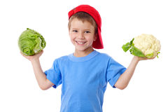 Smiling kid with cabbage and cauliflower Stock Photos