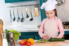smiling kid in chef hat and apron cooking vegetable salad stock image