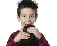 Smiling kid eating chocolate Stock Images