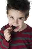 Smiling kid eating chocolate Royalty Free Stock Images
