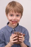 Smiling kid eating chocolate from jar. Royalty Free Stock Photography