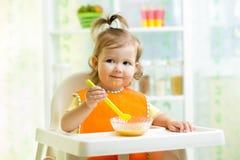 Smiling kid eating food on kitchen. Smiling kid girl eating food on kitchen stock photography
