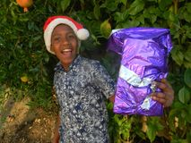 Smiling kid in Father Christmas hat holding Christmas present royalty free stock images