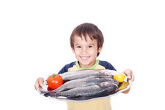 Smiling kid with fresh fish on table. Smiling kid with fresh fish, lemon and tomato on table Royalty Free Stock Photo