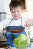 Smiling kid with frying-pan Stock Photography
