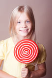 Smiling kid girl eating lollipop on beige Royalty Free Stock Photography
