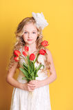 Smiling kid girl holding flowers on yellow Stock Image