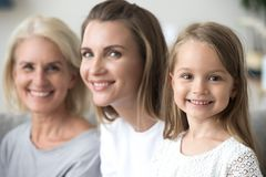 Smiling kid girl looking at camera with mother and grandmother stock photo