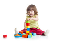 Smiling kid girl playing building block toys stock images
