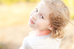 Smiling kid girl posing outdoors. On nature background Stock Photos