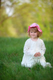 Smiling kid girl  wearing stylish white dress sitting in the gra Stock Photo