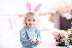 Funny kid girl in room. Smiling kid girl 3-4 year old holding Easter eggs and wearing rabbit ears closeup. Looking at camera royalty free stock photo