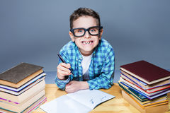 Smiling kid in glasses doing homework at the desk Royalty Free Stock Photo
