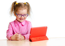 Smiling kid in glasses looking at mini tablet pc screen sitting Royalty Free Stock Photos