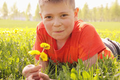 Smiling kid on grass with dandelions Royalty Free Stock Image