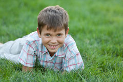 Smiling kid on the green grass Stock Photography