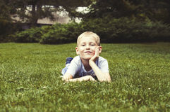 Smiling kid on a green grass Royalty Free Stock Image