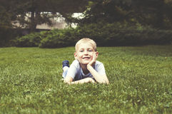 Smiling kid on a green grass Stock Photo