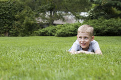 Smiling kid on a green grass Royalty Free Stock Images