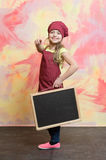 Smiling kid, happy girl cook in red chef hat, apron Stock Images
