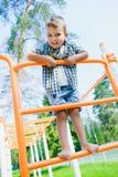 Smiling kid having fun at playground. Child doing gymnastic exercises Stock Image