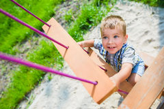 Smiling kid having fun at playground. Child doing gymnastic exercises Stock Photography